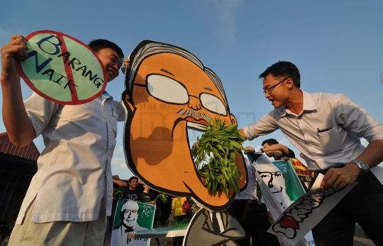 Machang Bubok assemblyman Lee Khai Loon (right) puts some kangkung into the mouth of a mock figure of Najib during the flash mob to protest price hikes. - The Malaysian Insider pic by Hasnoor Hussain, January 15, 2014.